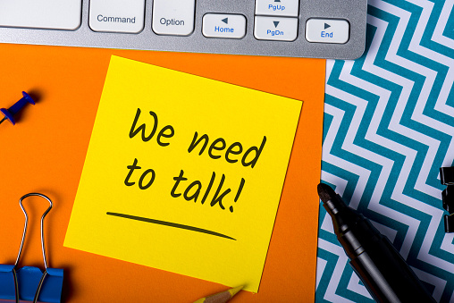 We need to talk. Note on workplace. notification of a serious conversation.