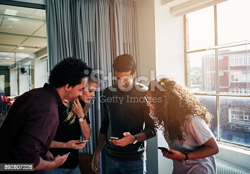 Shot of a group of colleagues using their cellphones together in a modern office