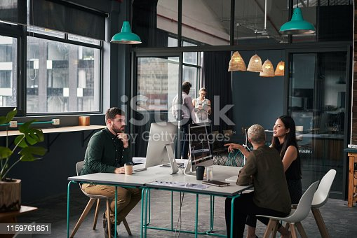 Cropped shot of a group of young businesspeople sitting and talking with each other while in the office