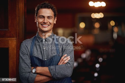 Shot of a confident young business owner standing with his arms folded under a doorway at a beer brewery during the day