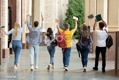 istock We passed exams. Students raised hands and walking in campus 1175434162