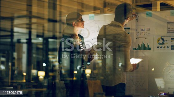 Cropped shot of two business colleagues standing and using a whiteboard and technology to brainstorm in the office at night