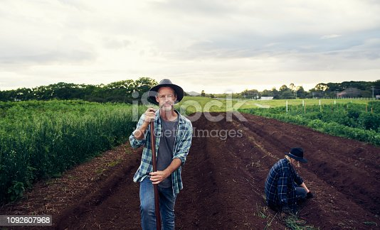 Portrait of a mature man and a young woman tending to crops on a farm
