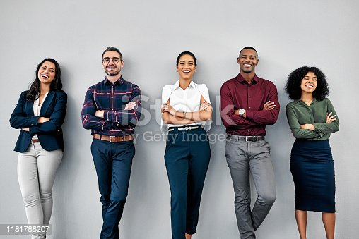Studio shot of a group of businesspeople standing in line against a grey background