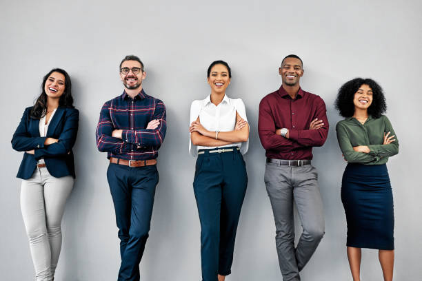 We put the human in human resources Studio shot of a group of businesspeople standing in line against a grey background young adult stock pictures, royalty-free photos & images