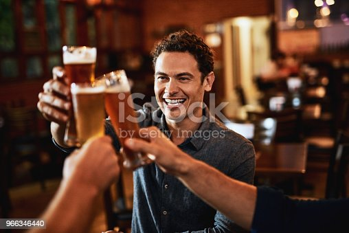 Shot of a group of young friends seated at a table together while enjoying a beer and celebrating with a celebratory toast inside a bar