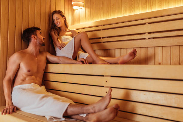 We should do this more often Happy young couple enjoying a sauna at a spa resort. sauna stock pictures, royalty-free photos & images
