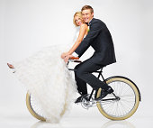 Cute young newlyweds riding a vintage bicycle together - portrait