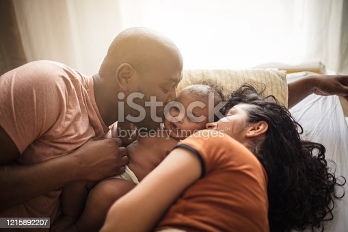 We stick together. African American parents with daughter on bed.
