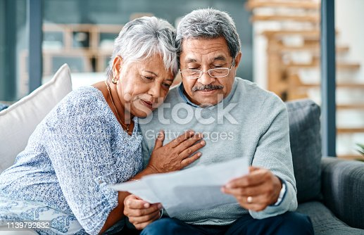Shot of a mature couple looking worried while going through paperwork together at home