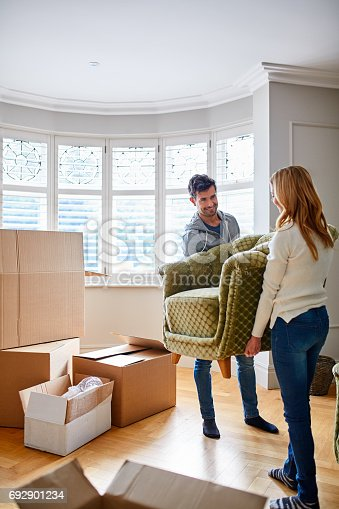 Shot of a happy young couple carrying a chair in their new house