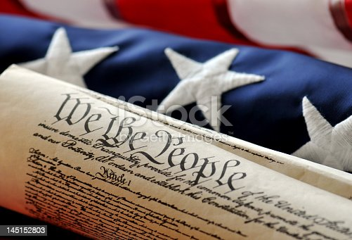 American Constitution with US Flag. Focus on document with stars and stripes in background.