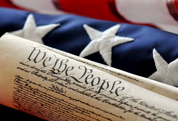 We The People - US Constitution American Constitution with US Flag. Focus on document with stars and stripes in background. independence day photos stock pictures, royalty-free photos & images