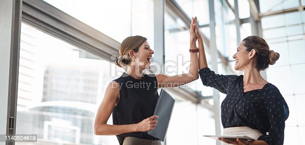 Shot of two well-dressed businesspeople high fiving in the office