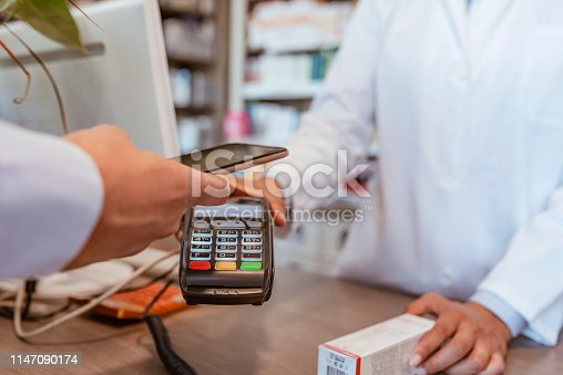 Wireless payment using a smartphone and NFC technology. Close up. Male Customer paying with a smartphone in pharmacy. Close Up shopping. Modern technology and people concept - Woman with the payment terminal and male customer with smartphone paying for medications.