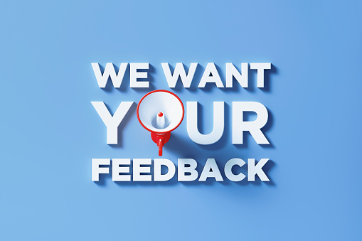 We Want Your Feedback written by red megaphone on blue background. Horizontal composition with copy space. Great use for survey, assessment and questionnaire concepts.