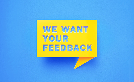 We want your feedback written yellow chat bubble on blue background. Horizontal composition with copy space. Feedback concept.