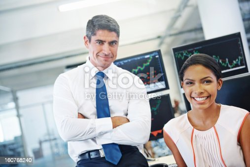 Portrait of two positive-looking financial officers in front of monitors displaying stock information