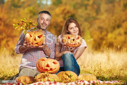 lifestyle, fun and joyful moments in nature with young couple holding Halloween pumpkins and smiling.