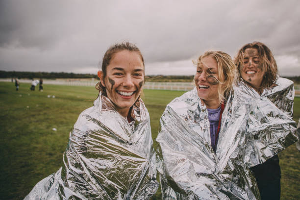 We Won! Women are wrapped up in foil blankets after completing a charity obstacle course. One of the women is looking at the camera and they are all covered in mud. mud run stock pictures, royalty-free photos & images