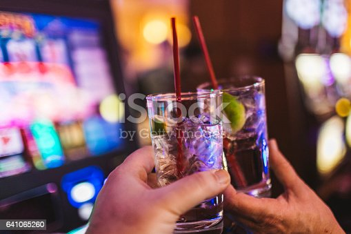 In a Las Vegas casino, cheering couple who just won big money at a slot machine. They each have a glass of gin and tonic in their hands. Faces are not visible