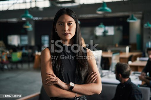 Cropped portrait of an attractive young businesswoman standing in her office while her colleagues work behind her during the day