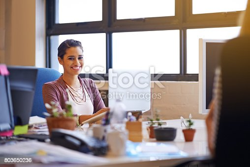 Shot of a young woman working on her laptop in the office and looking at the camera