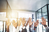 Closeup shot of a group of businesspeople raising their hands in an office
