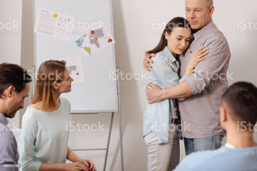 Weak brunette nestling up to her colleague stock photo