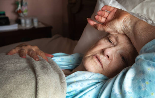weak feverish elderly woman in bed covering her forehead with her arm - mulher deixar ir imagens e fotografias de stock