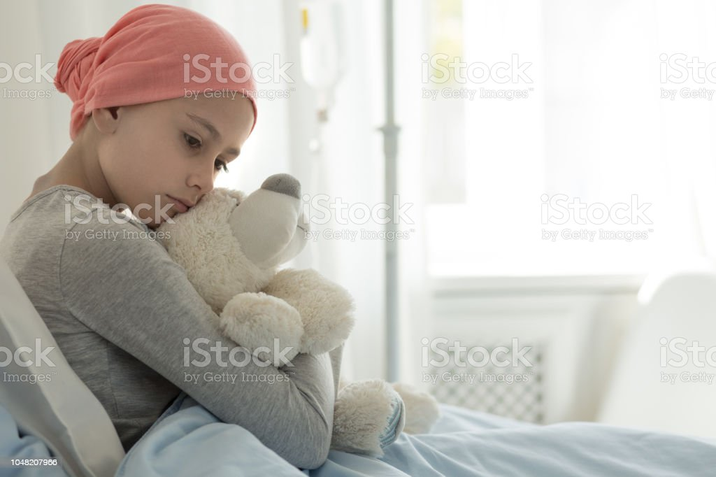 Weak girl with cancer wearing pink headscarf and hugging teddy bear – zdjęcie