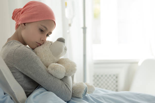Weak girl with cancer wearing pink headscarf and hugging teddy bear stock photo