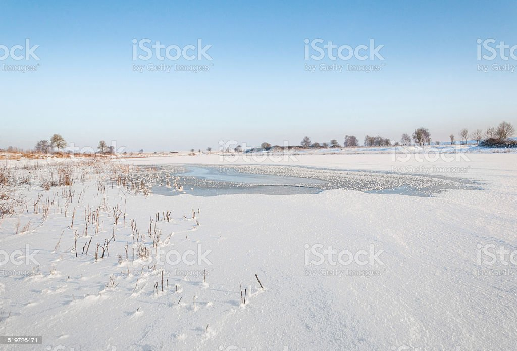 Weak spot in the snow covered ice stock photo