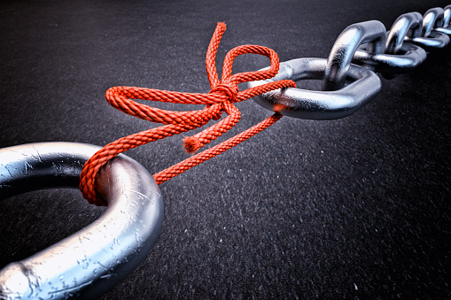 Metallic chain connected by a red knotted rope on black background