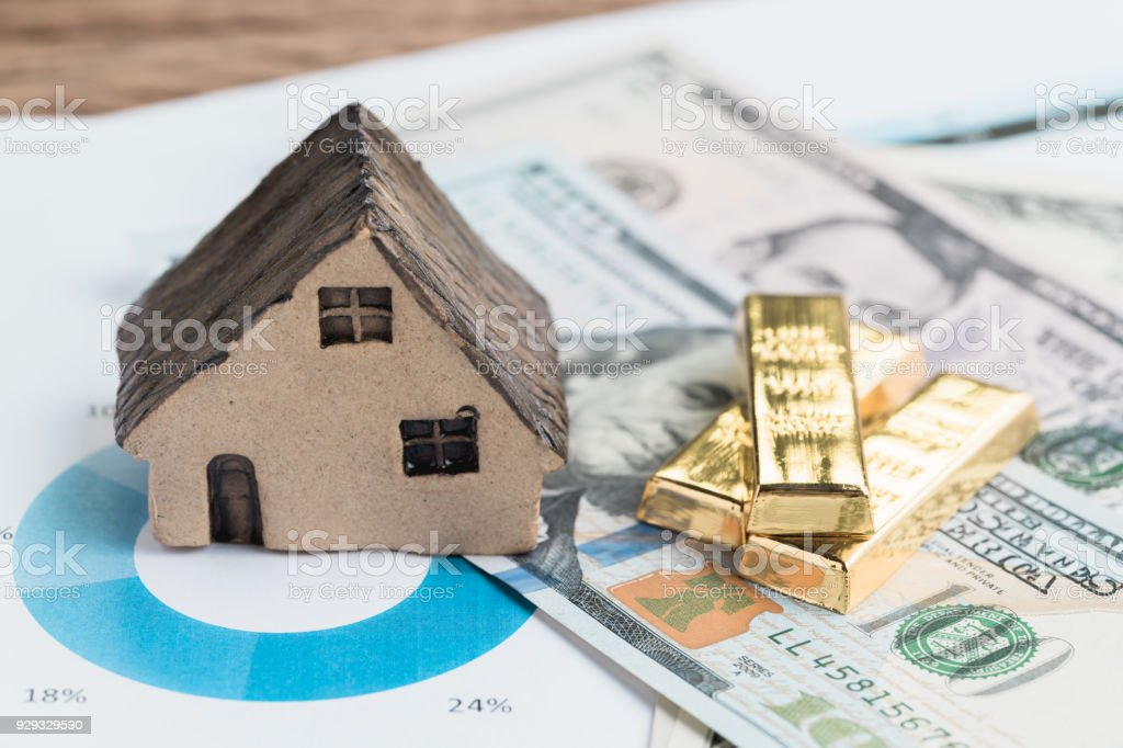 Wealth management or investment asset allocation concept, house, gold bars ingot on pile of US dollar bills on percentage pile chart using in balance risk and rich in financial investment idea stock photo