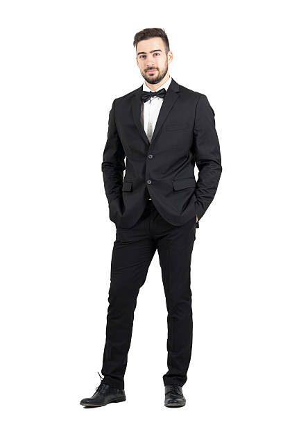 wealthy confident relaxed young man in tuxedo looking at camera - tuxedo stock photos and pictures