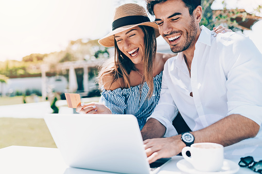 Wealthy young couple with credit card and laptop