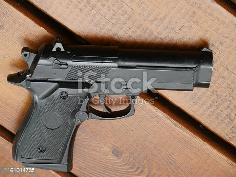 black handgun on wooden table close to