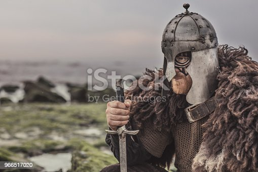 istock Weapon wielding bloody medieval warrior alone on a cold seashore 966517020