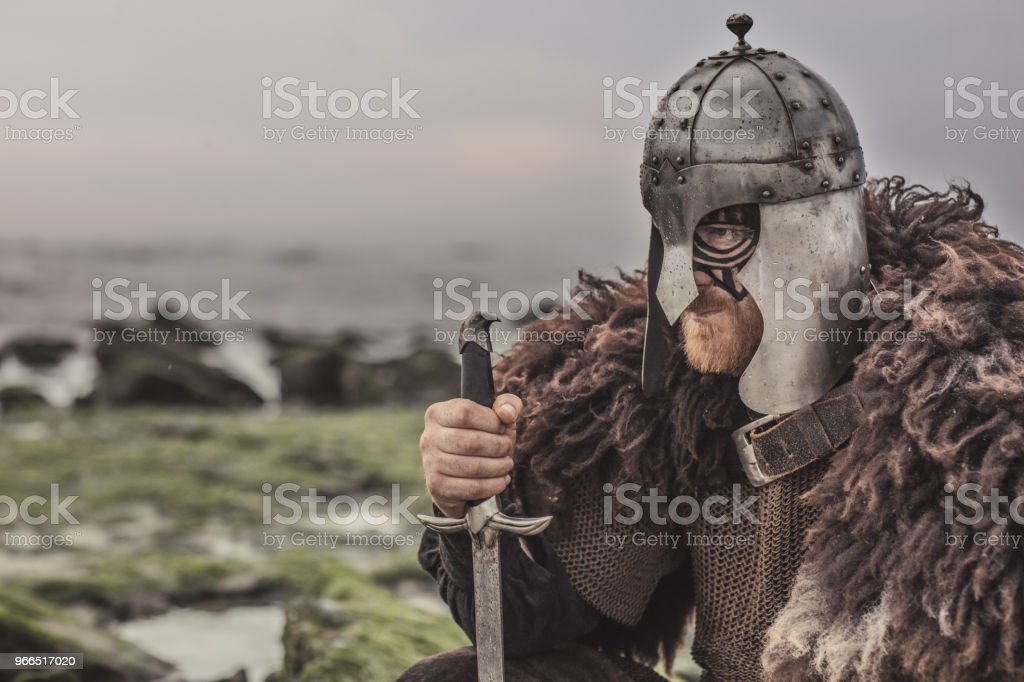 Weapon wielding bloody medieval warrior alone on a cold seashore stock photo