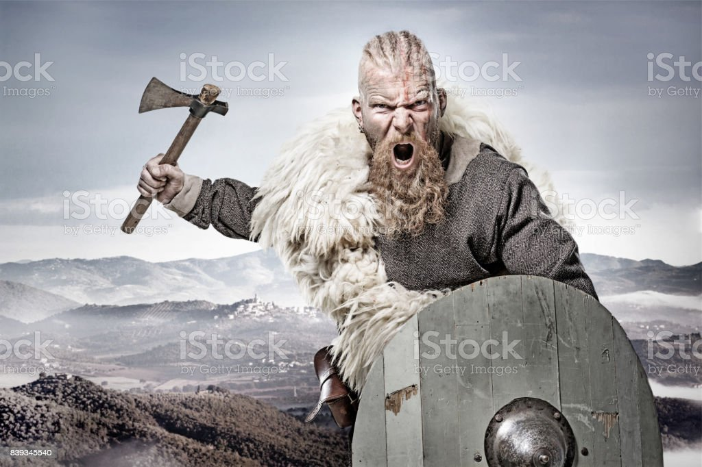 Weapon wielding bloody viking warrior in emotional pose against mountain range stock photo