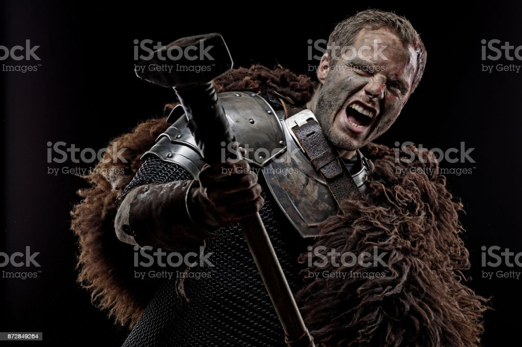 Weapon wielding dirty bloody viking warrior in emotional pose stock photo