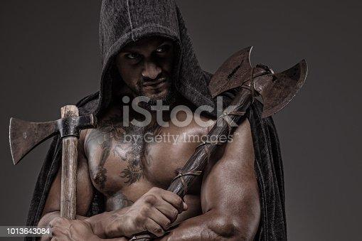 Weapon wielding Indian Descent warrior barbarian king alone in studio shoot