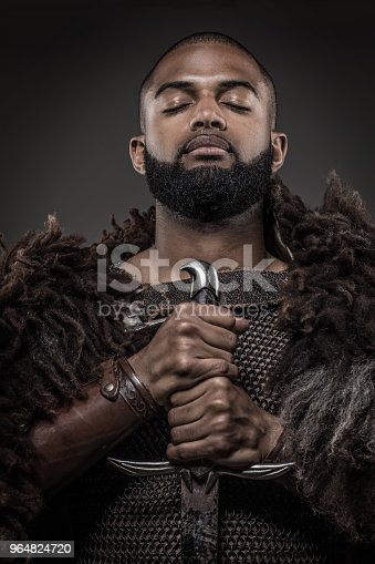 Weapon wielding viking inspired black warrior alone in front of a mountain range