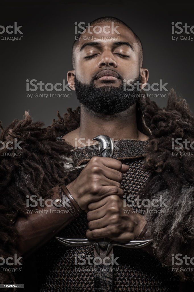 Weapon wielding viking inspired black warrior alone in front of a mountain range stock photo