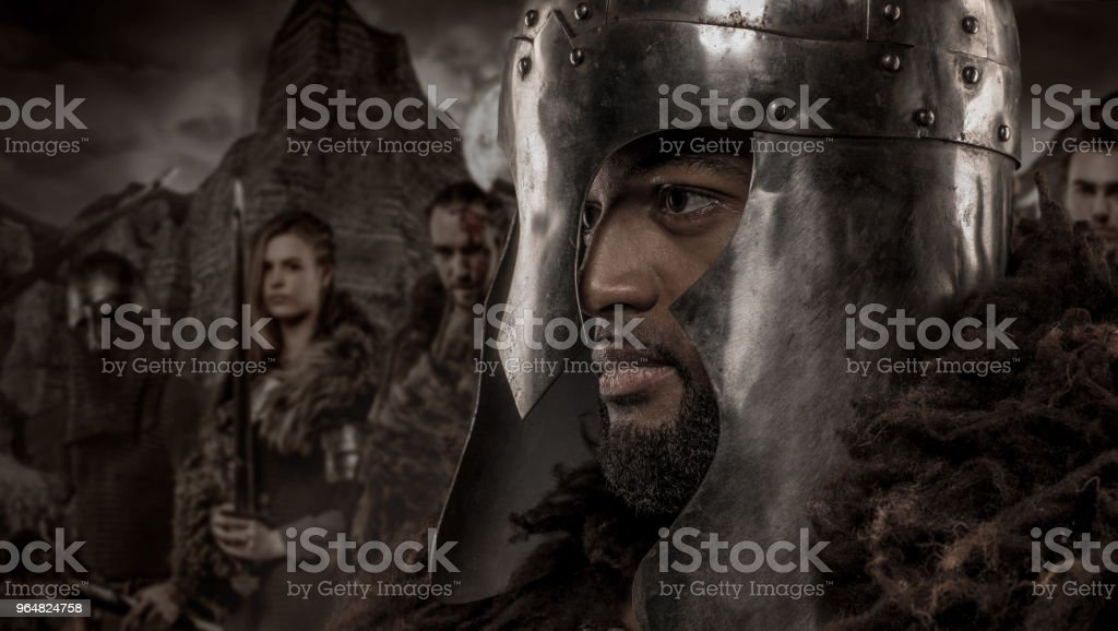 Weapon wielding viking inspired black warrior alone in front of a mountain range and clan royalty-free stock photo