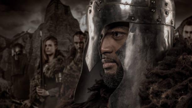 waffe schwingt viking inspiriert schwarze krieger alleine vor einer bergkette und clan - filmplakate stock-fotos und bilder