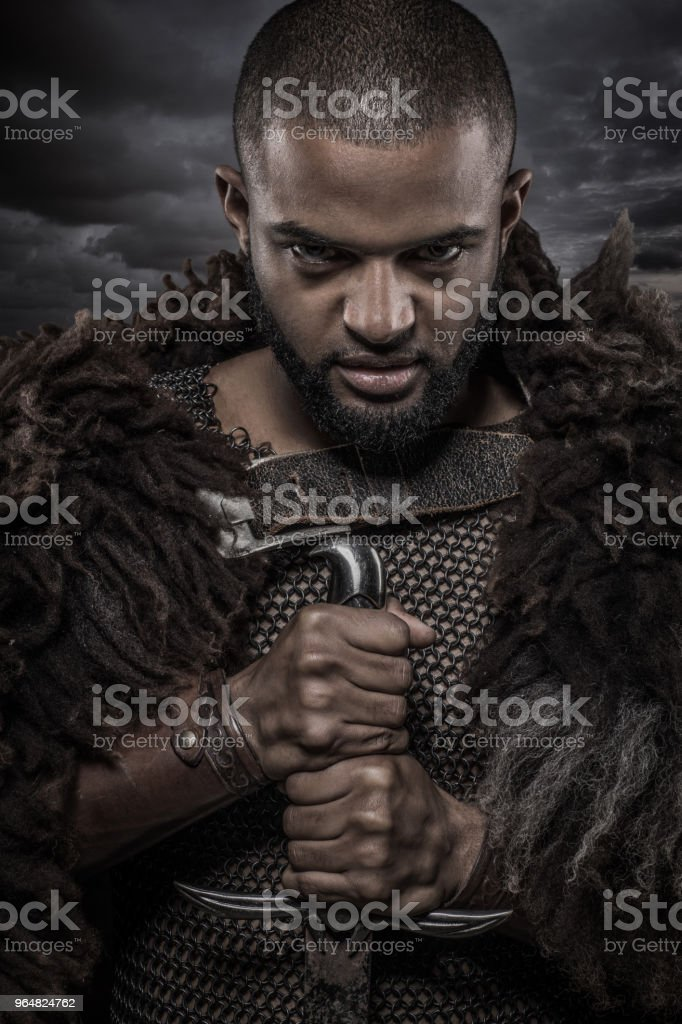 Weapon wielding viking inspired black warrior alone in front of a cloudy sky royalty-free stock photo