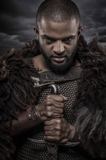 weapon wielding viking inspired black warrior alone in front of a cloudy sky - principe persona nobile foto e immagini stock