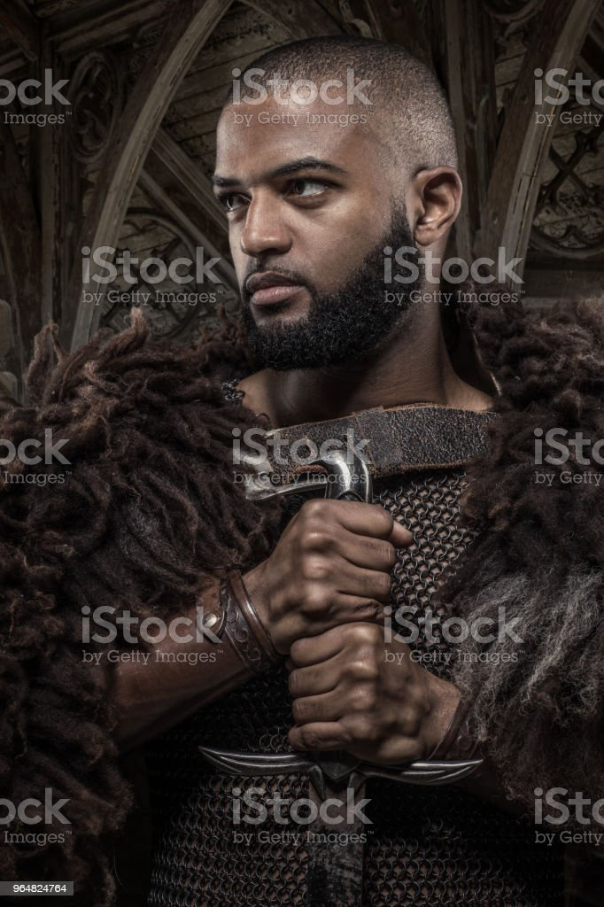 Weapon wielding viking inspired black warrior alone in front of a mountain range royalty-free stock photo
